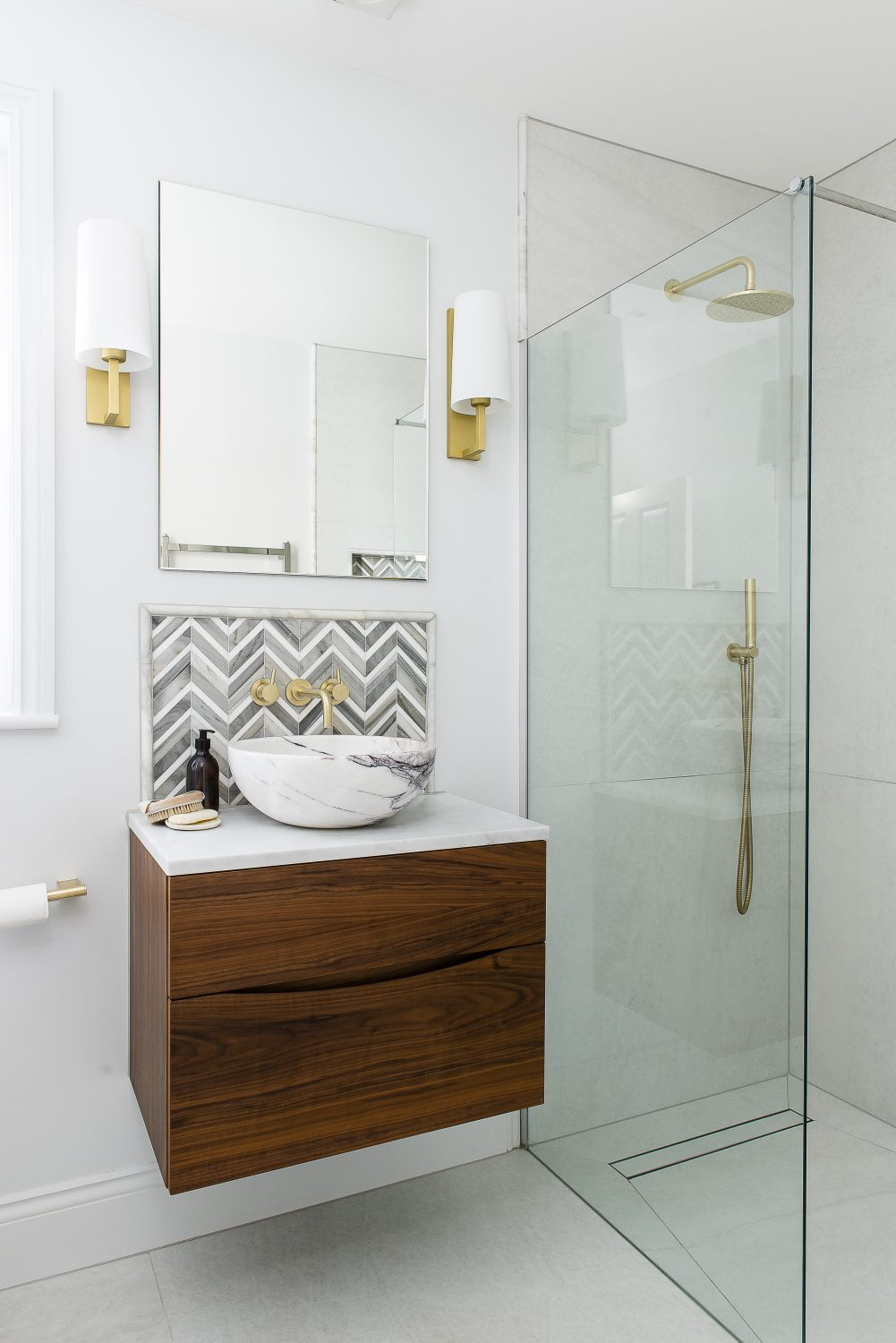 The master bedroom en suite features a Carrara marble bowl basin on top of a walnut wood floating cabinet, with small marble tiles from Mandarin Stone in a herringbone pattern as a splashback