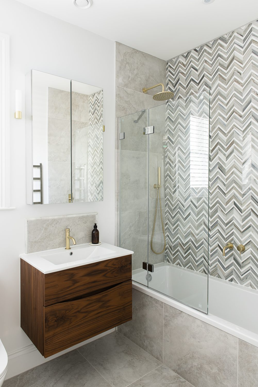 The same herringbone tiles form a beautiful backdrop to the bath and shower in a guest bathroom