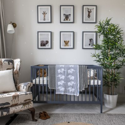 The nursery wallpaper features subtle polka dots on a soft grey background. Zoe had the chair reupholstered in African animal fabric