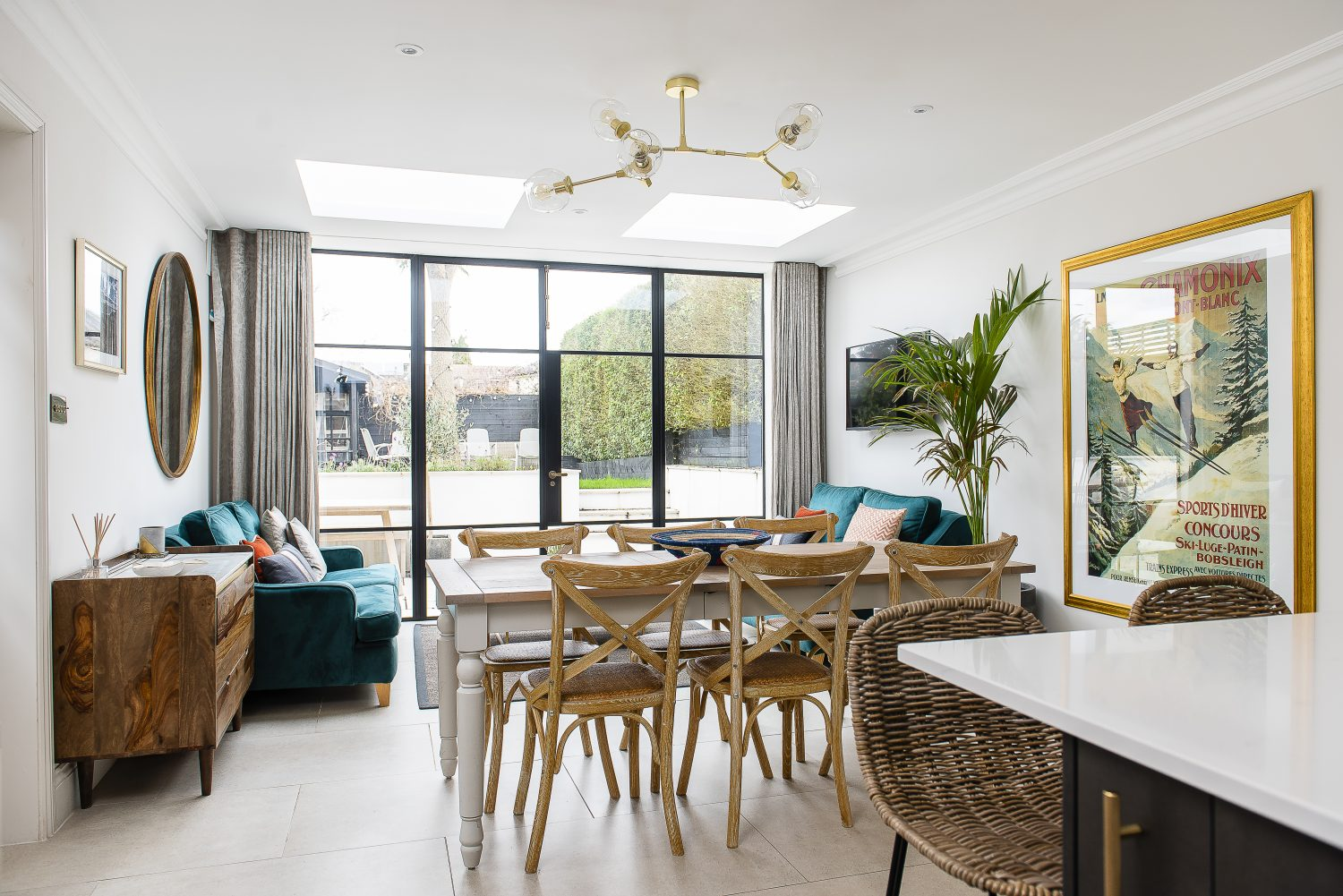 Crittall-style doors by Fabco Sanctuary lead out from the dining room into the raised garden. The amazing gold and glass light over the dining table is by Lindsey Adelman