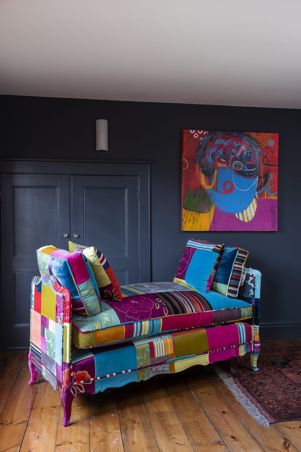 The brightly coloured patchwork day bed was created, bespoke, for Jane by Squint in Shoreditch. Hanging on the wall behind is an equally bright painting by Nathan Pendlebury