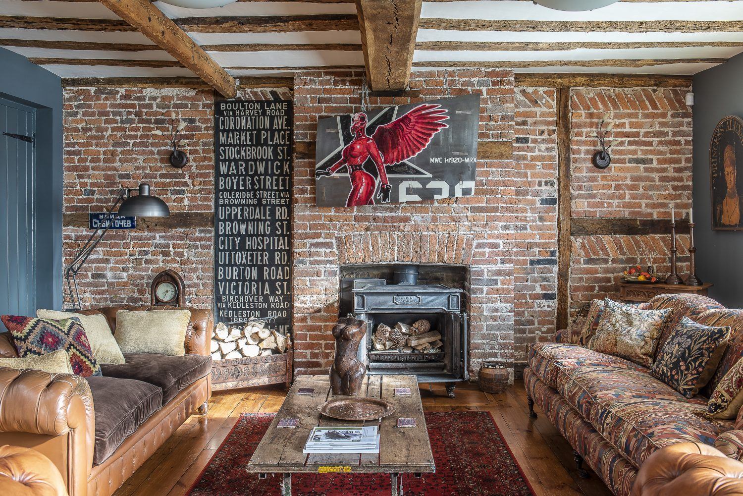A piece by the artist Wreckage, a member of an art co-operative called the Mutoid Waste Company, painted on a panel of a fighter jet, hangs above the woodburner in the sitting room