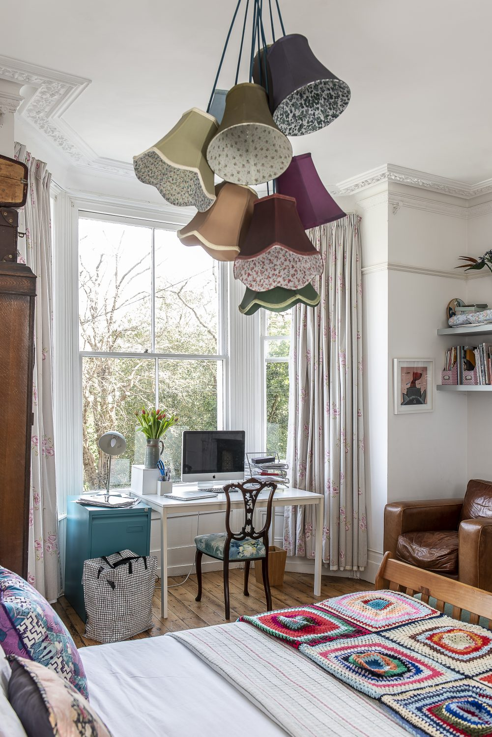 A cluster of mismatched floral lampshades that Sadie found on notonthehighstreet.com hangs from the soaring ceiling in this peaceful bedroom
