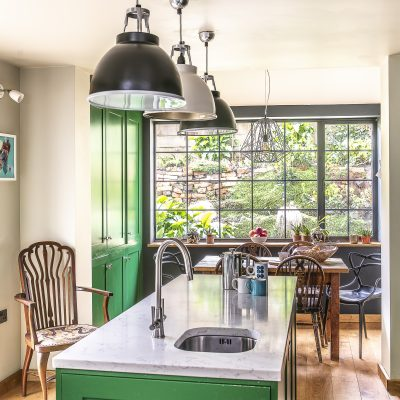 The cabinet work and cupboards in the kitchen have all been painted in a bright grass green, Sadie's favourite colour, with black accent walls around the range cooker and the picture window