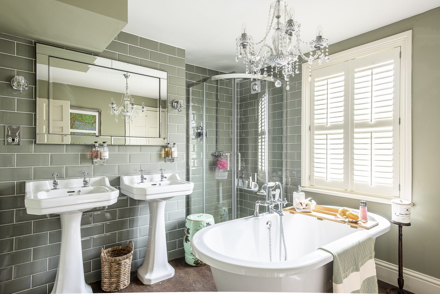 The bathroom, previously a bedroom, is now a sleek and luxurious space with pale, olive green tiles and gleaming sanitaryware