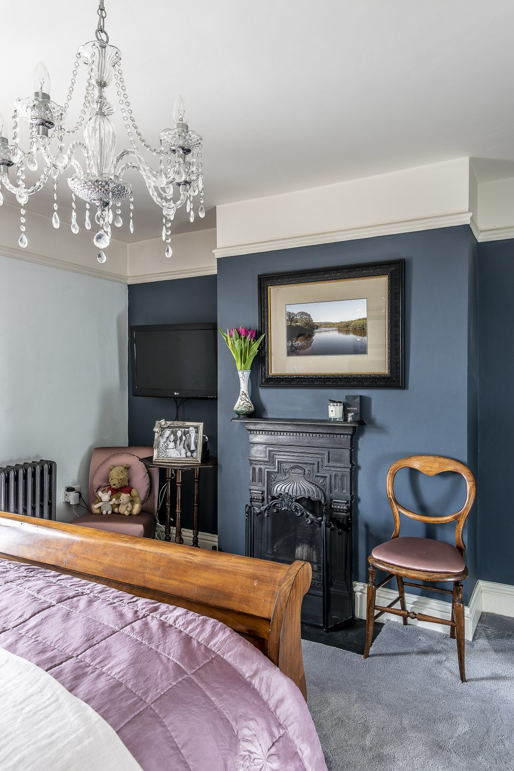 In the restful master bedroom an inky-blue wall and period fireplace have replaced built-in wardrobes