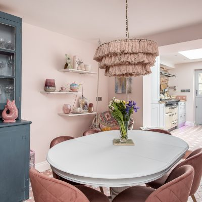 A huge pink lampshade by Anthropologie hovers over the dining table. The tiles on the walls in the kitchen, from Bert & May, miraculously match the floor tiles