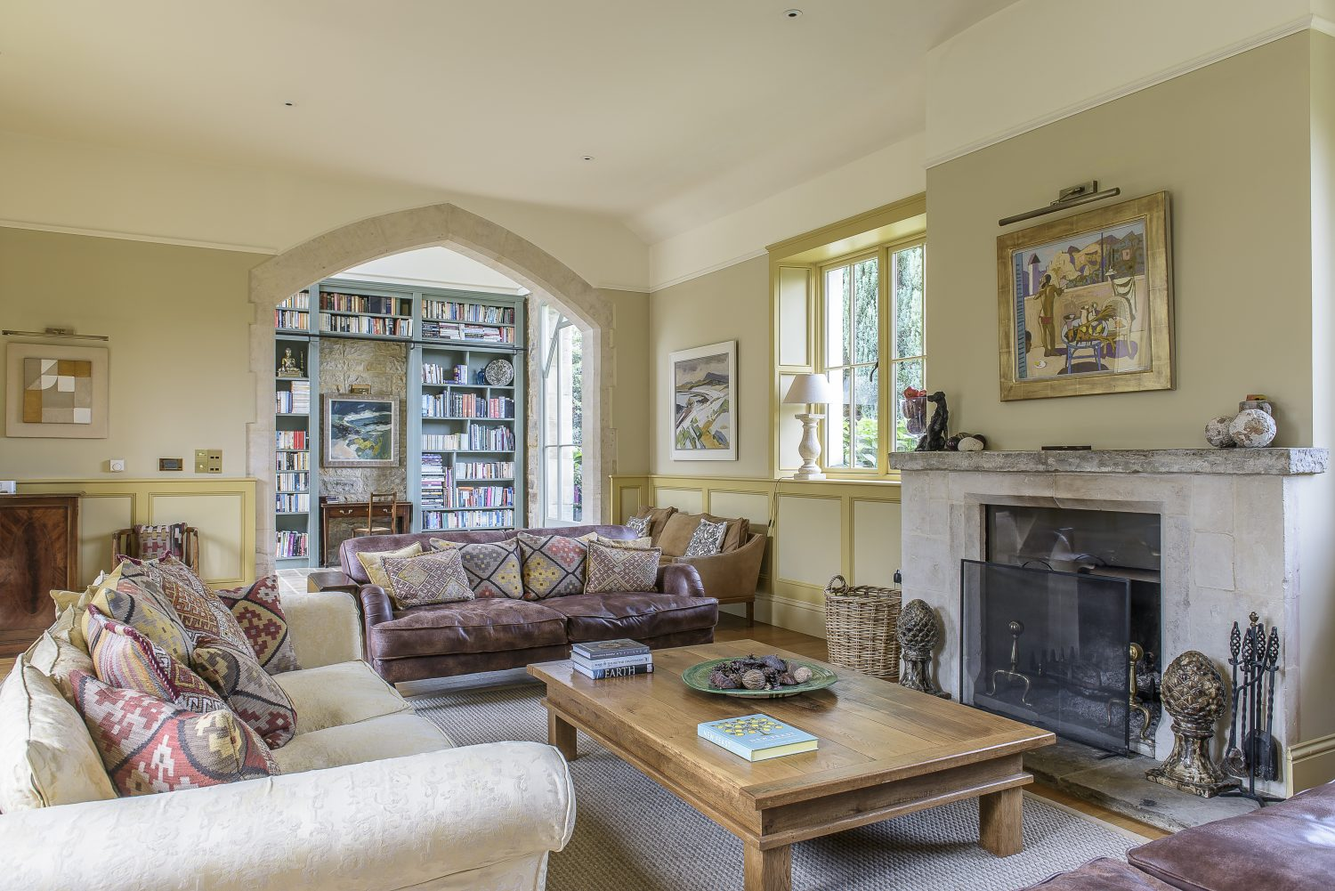 The sitting room is a lovely lofty space, with a stone mantelpiece flanked by three generous sofas piled with kilim cushions