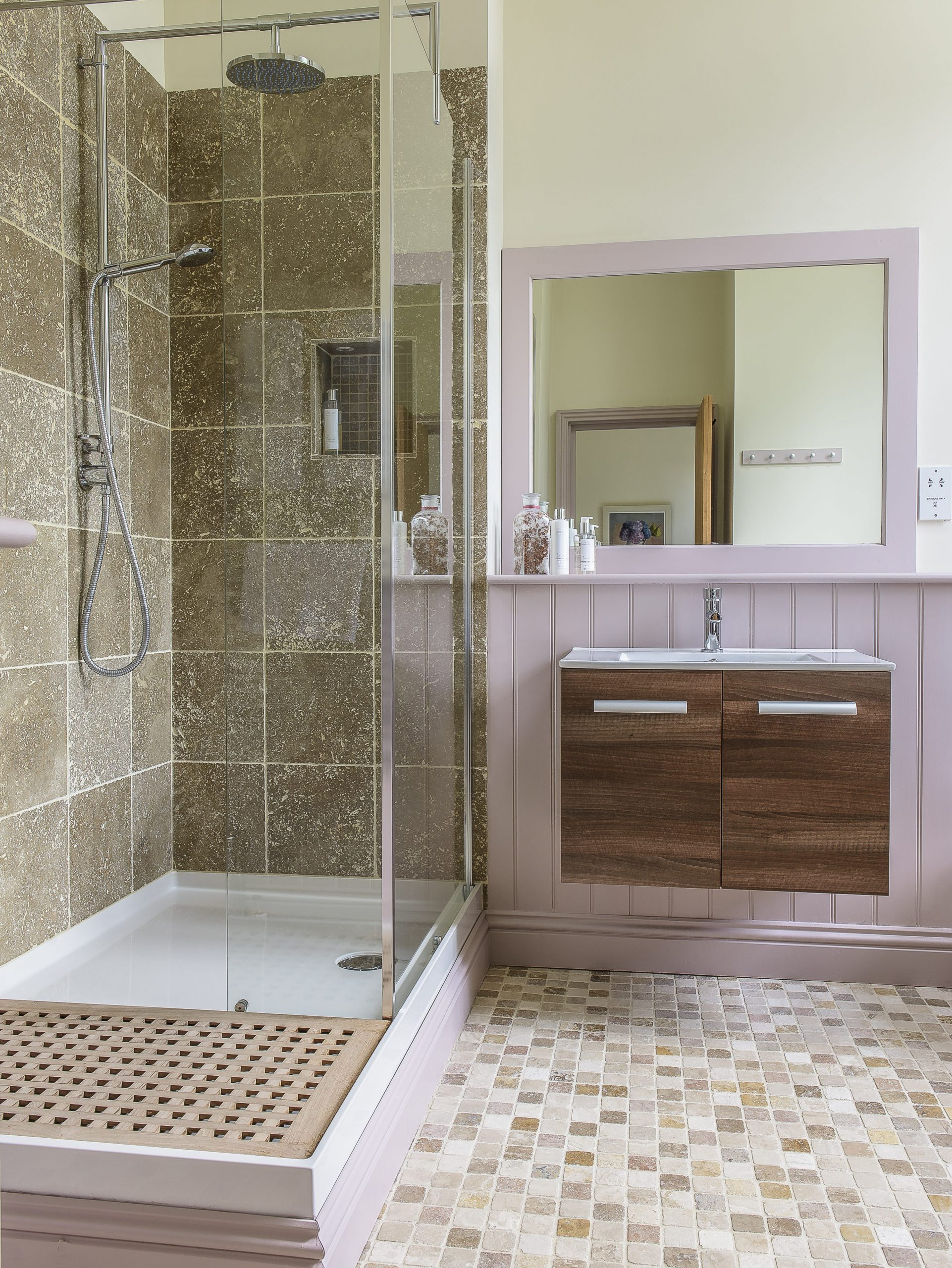 Pale pink panelling coupled with natural stone tiling and warm woods gives the en suite bathroom cosy appeal