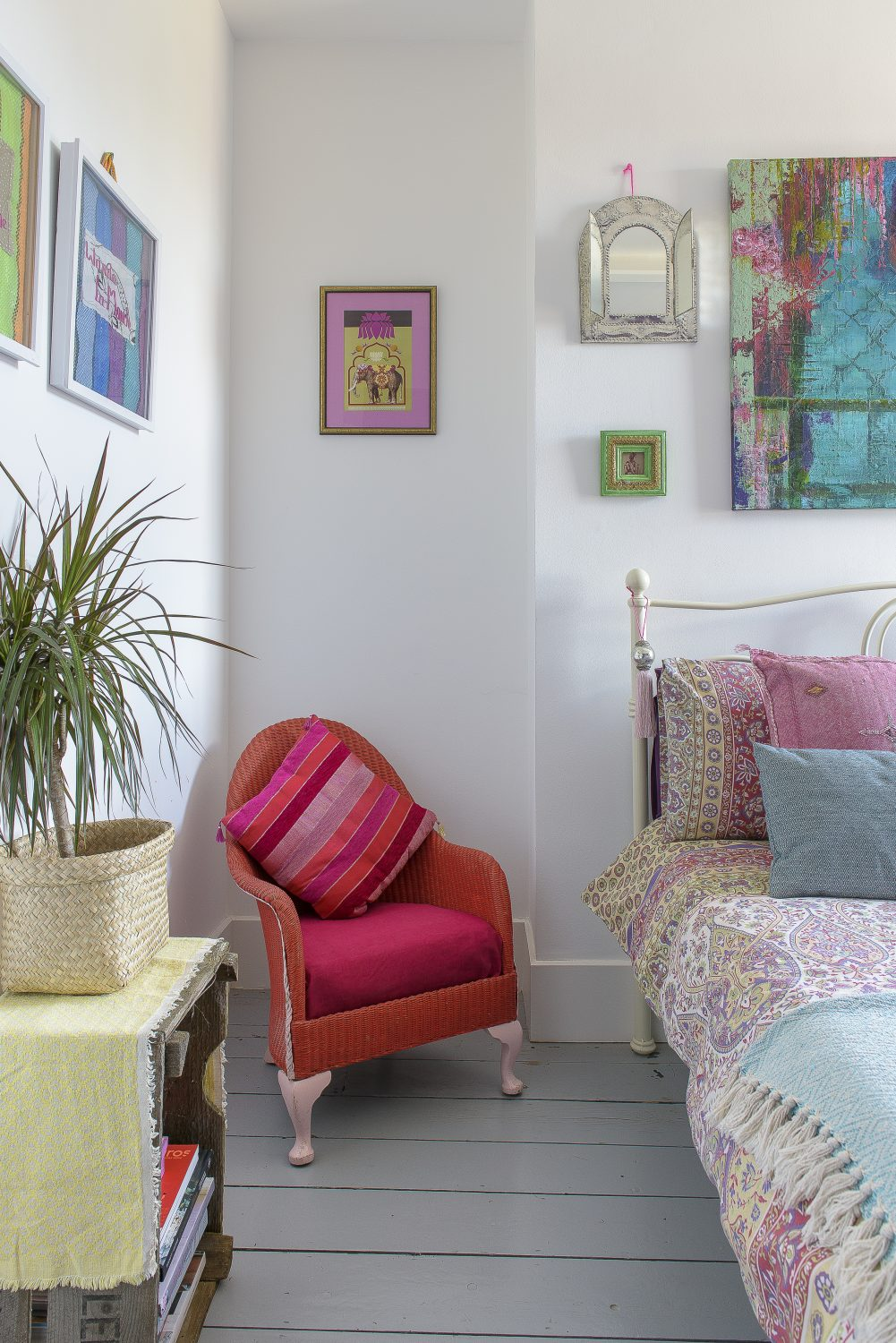 A colourful guest bedroom is filled with artworks collected on the couple's travels