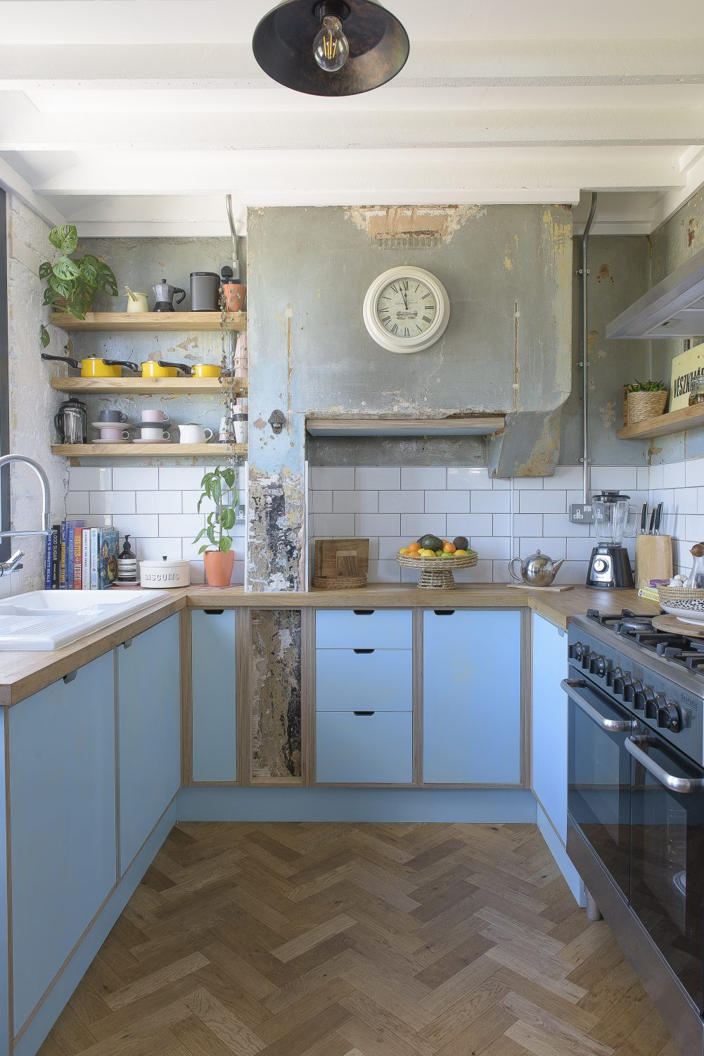 The kitchen is still in its original place in an extension at the back of the house. Cathe and John decided to keep the old plasterwork, where the bread oven used to be, and commissioned a new sky blue and wood contemporary kitchen with a herringbone parquet floor