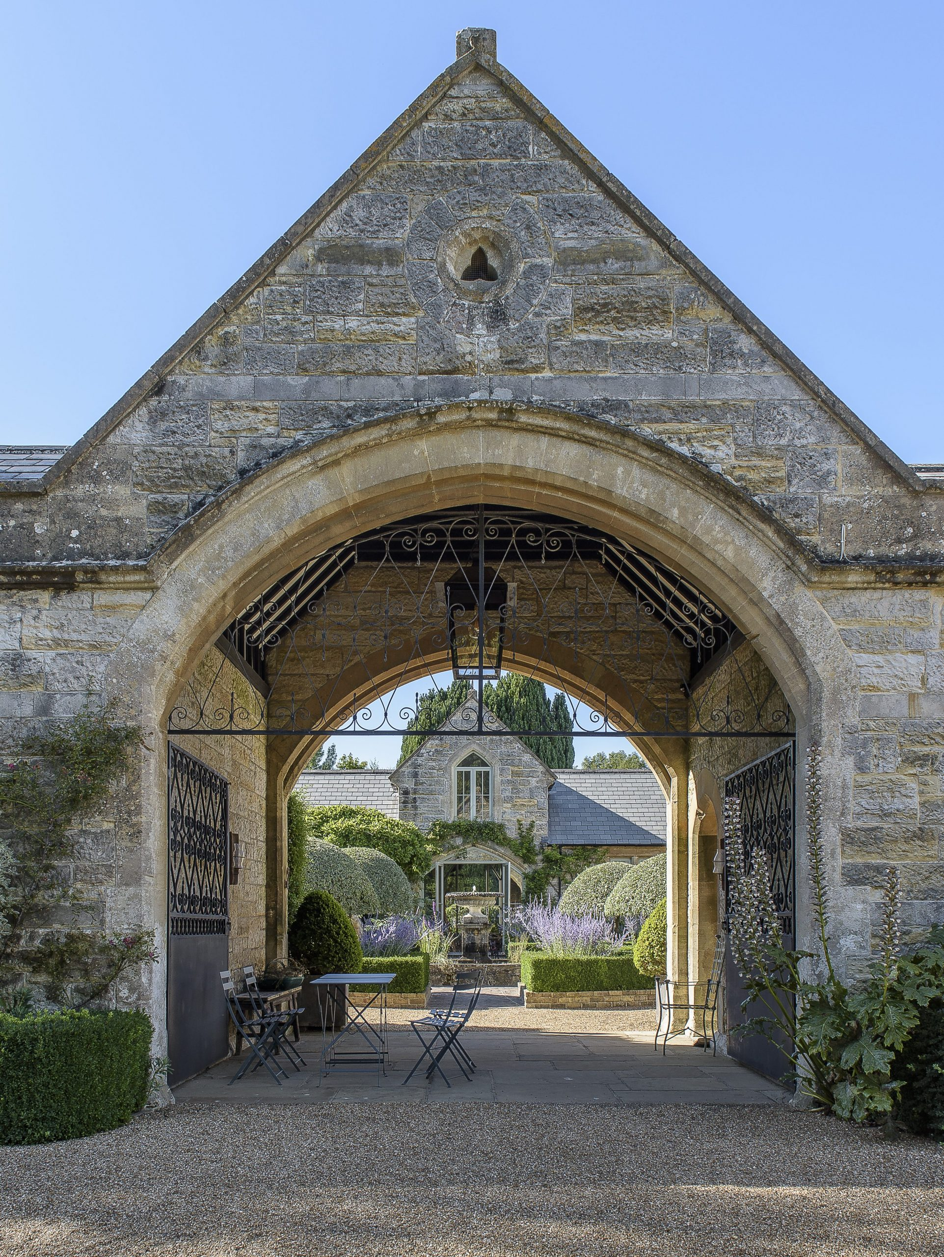 The archway entrance to the Italianate stone courtyard gives views through to the central fountain