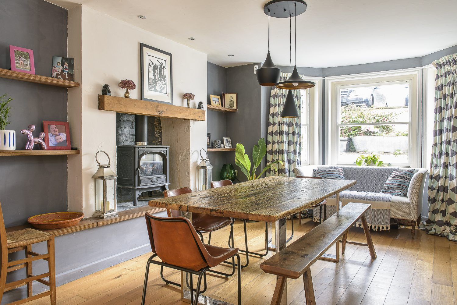 """When the couple moved in, the kitchen and dining room had already been opened out into a large family-friendly social space. A cosy touch is provided by the woodburner, nestled in an elevated position in the fireplace. The dining table was upcycled with the help of WildeWod Creations – a local small business that """"does wonders with wood,"""" says Jules. The walls are painted a deep grey, a colour picked out in the graphic pattern of the curtain fabric by Korla, also stocked at Haines Collection"""