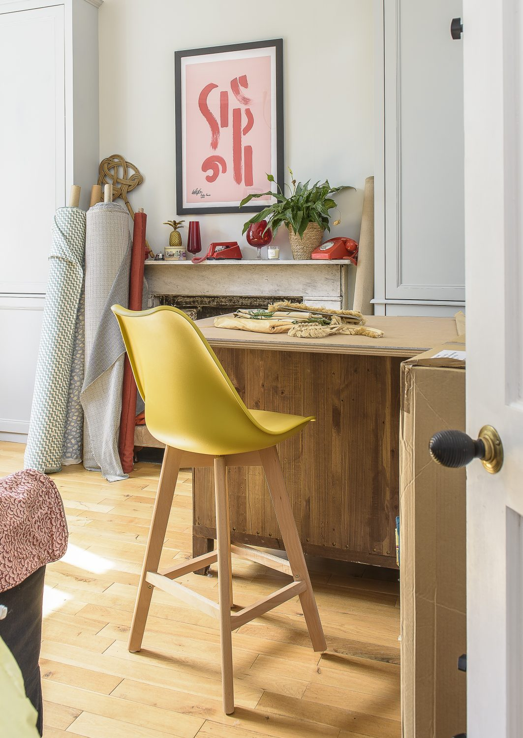 Jules made the fabric-cutting table in her workroom by putting a board on top of a chest of drawers that she bought from a British Heart Foundation furniture shop. The high stool was a Facebook Marketplace find