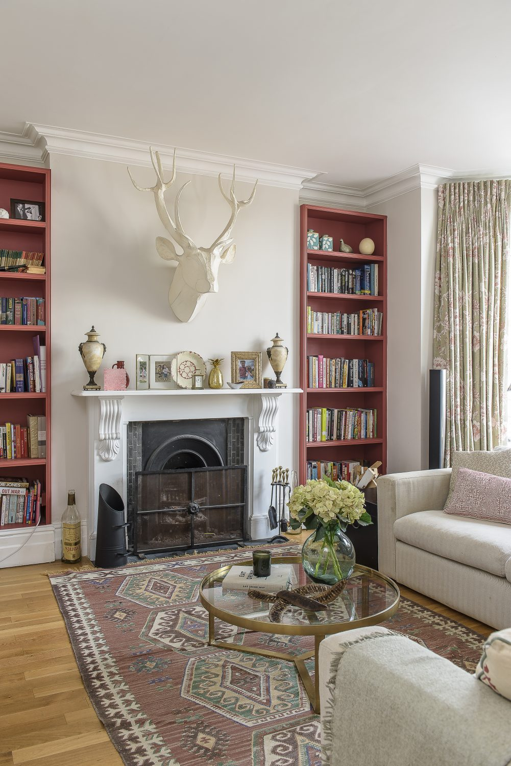 The high-ceilinged sitting room features a neutral colourway with bookshelves on either side of the original fireplace painted in Farrow & Ball Blazer