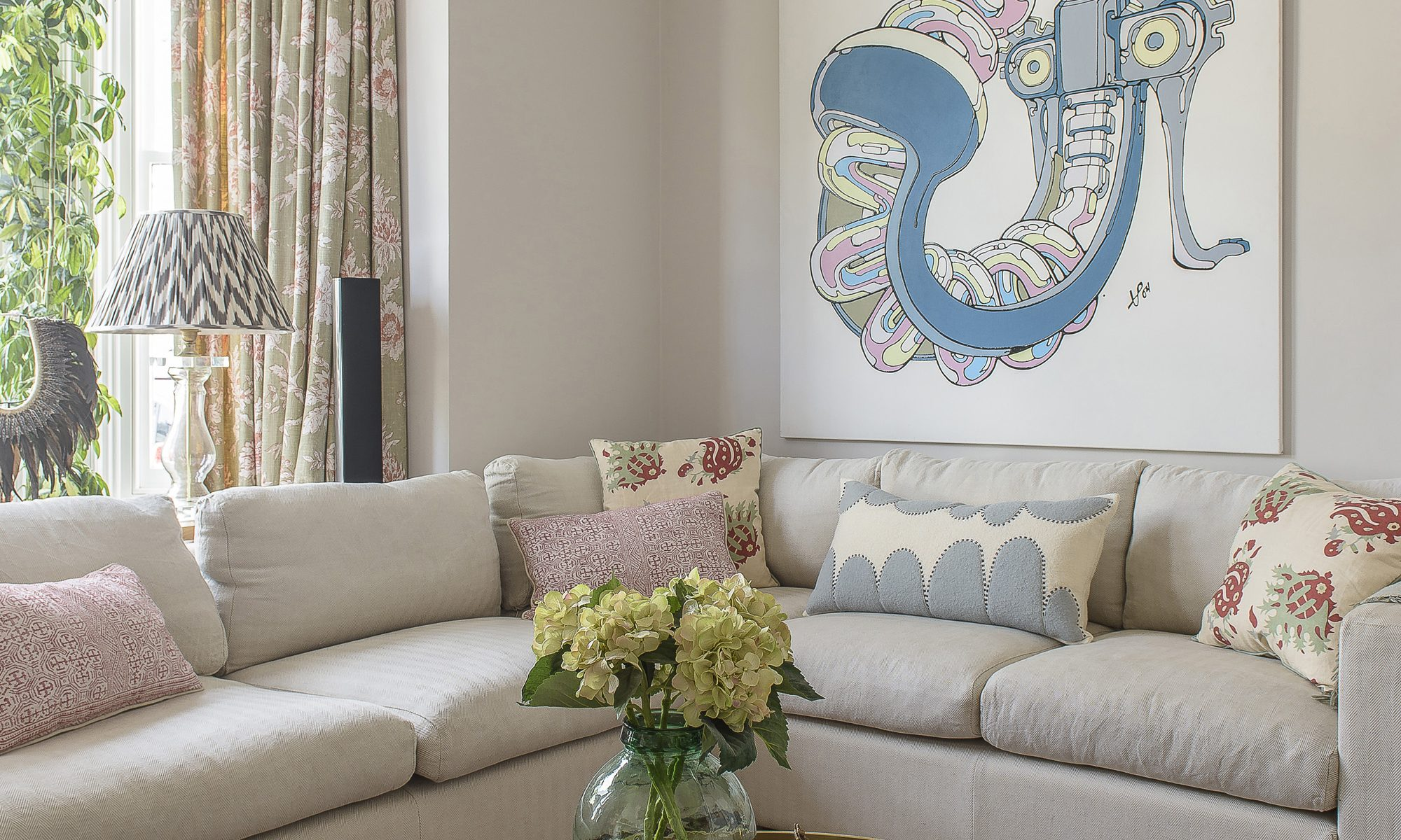 Pale blues and pinks that feature in a corkscrew print by London artist Tommy Penton in the sitting room are picked out in the room's soft furnishings. The cushions are from the Haines Collection and Fox Murray Home – a local lady who makes amazing, huge wool cushions