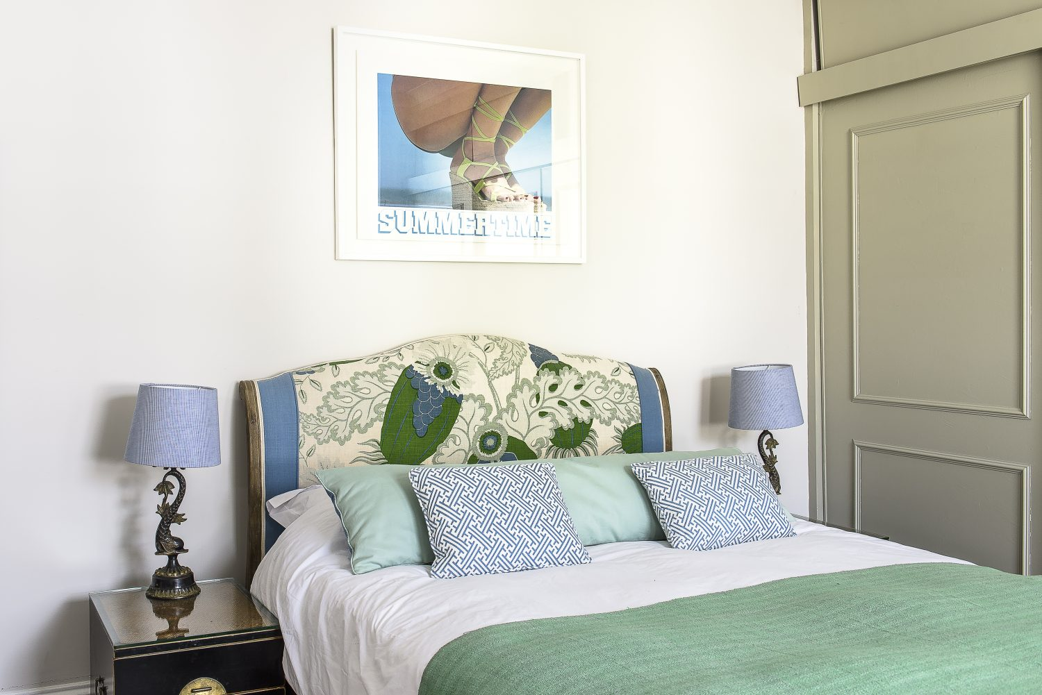 Jules re-covered the master bed's headboard that she bought from Loaf. The bedside tables are topped with bronze dolphin lamps, from unwanted stock that Jules sells on Haines Collection.