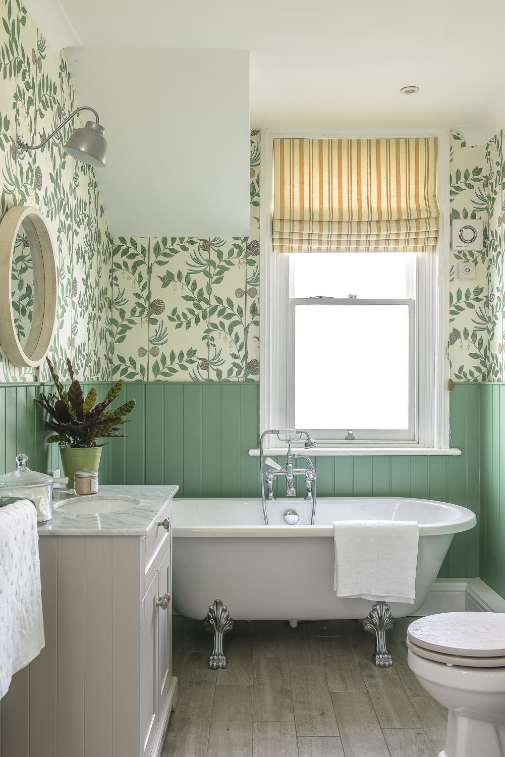 The family bathroom is an invitingly fresh space, with peppermint green tongue and groove panelling below Cole & Sons 'Secret Garden' wallpaper. The striped Roman blind is made from a Haines Collection fabric and the bath, marble-topped basin unit and taps are by Hudson Reed