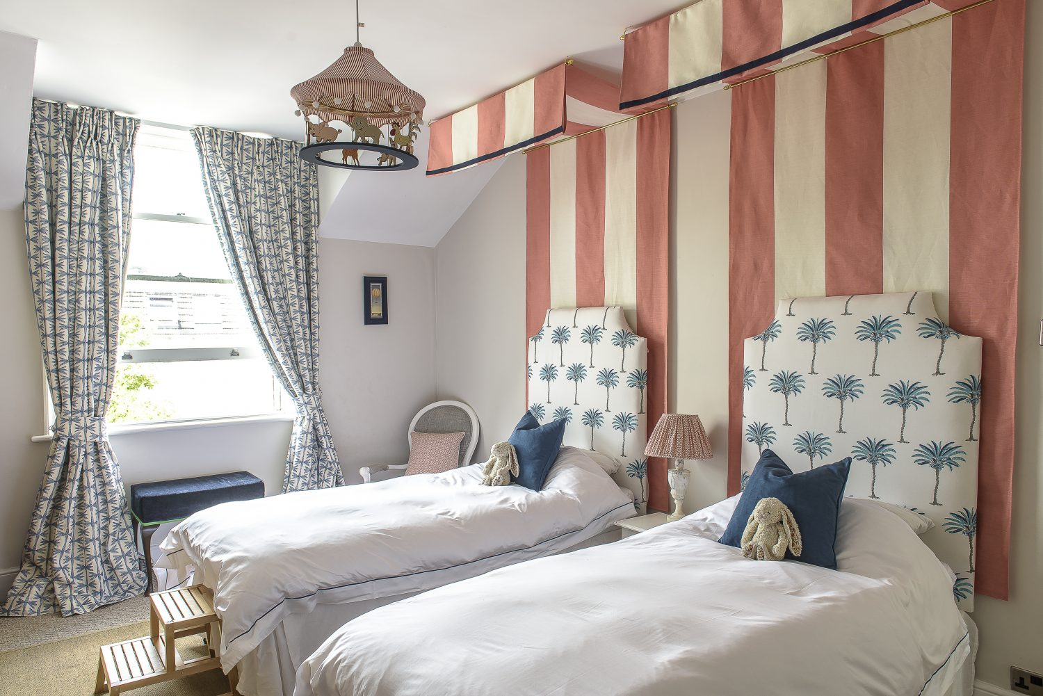 The couple's three-year-old daughter's gorgeous bedroom features twin beds with headboards made by Jules and upholstered in palm print fabric. Canopies reminiscent of circus stripes give a playful feel. The animal pendant light above the beds was found by Jules in a charity shop and customised with pom poms