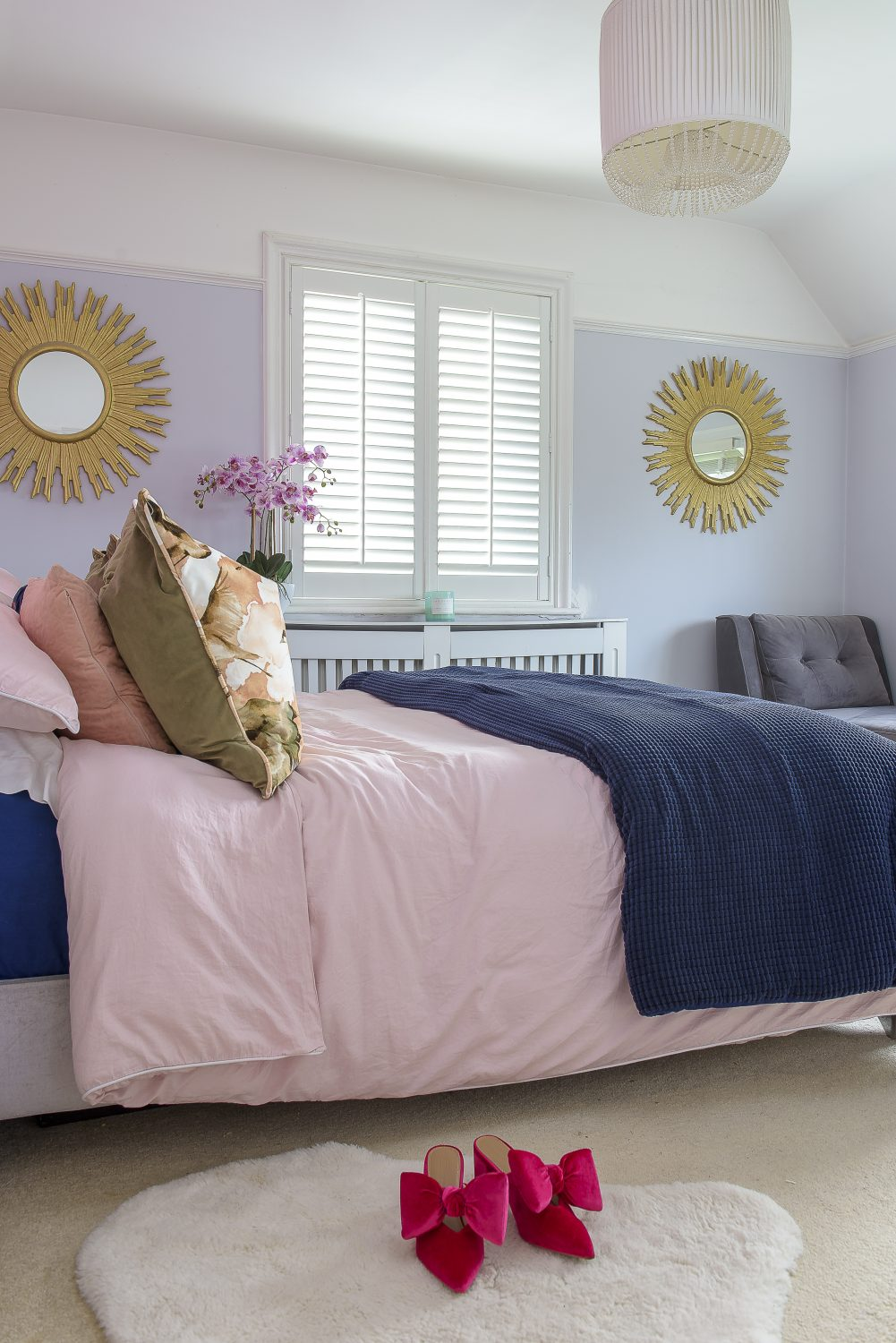 The master bedroom breaks from Cat's signature colour palette with soft lilac walls and accents of navy