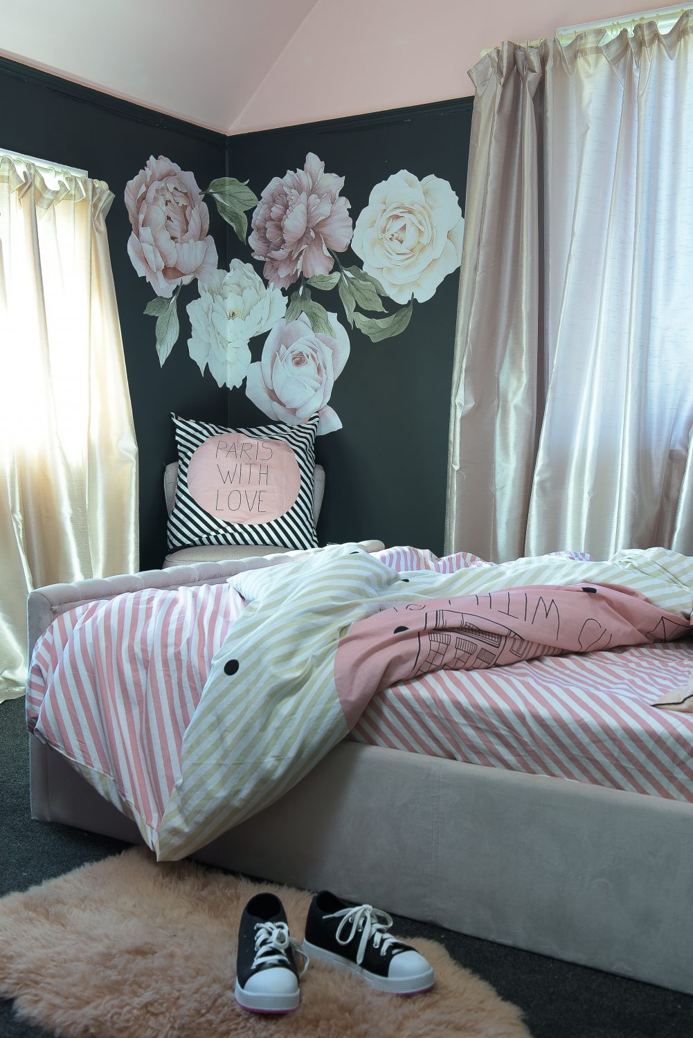 In the couple's eldest daughter's room, the carpets and walls are predominantly black with accents of pink and floor-length satin curtains