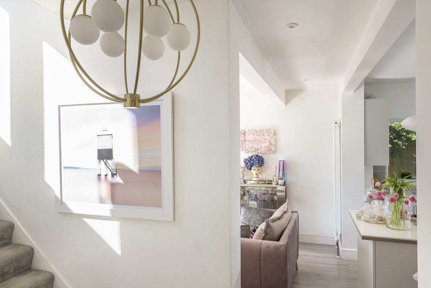 A crisp white interlude between the sitting room and kitchen space, the hallway is filled with light
