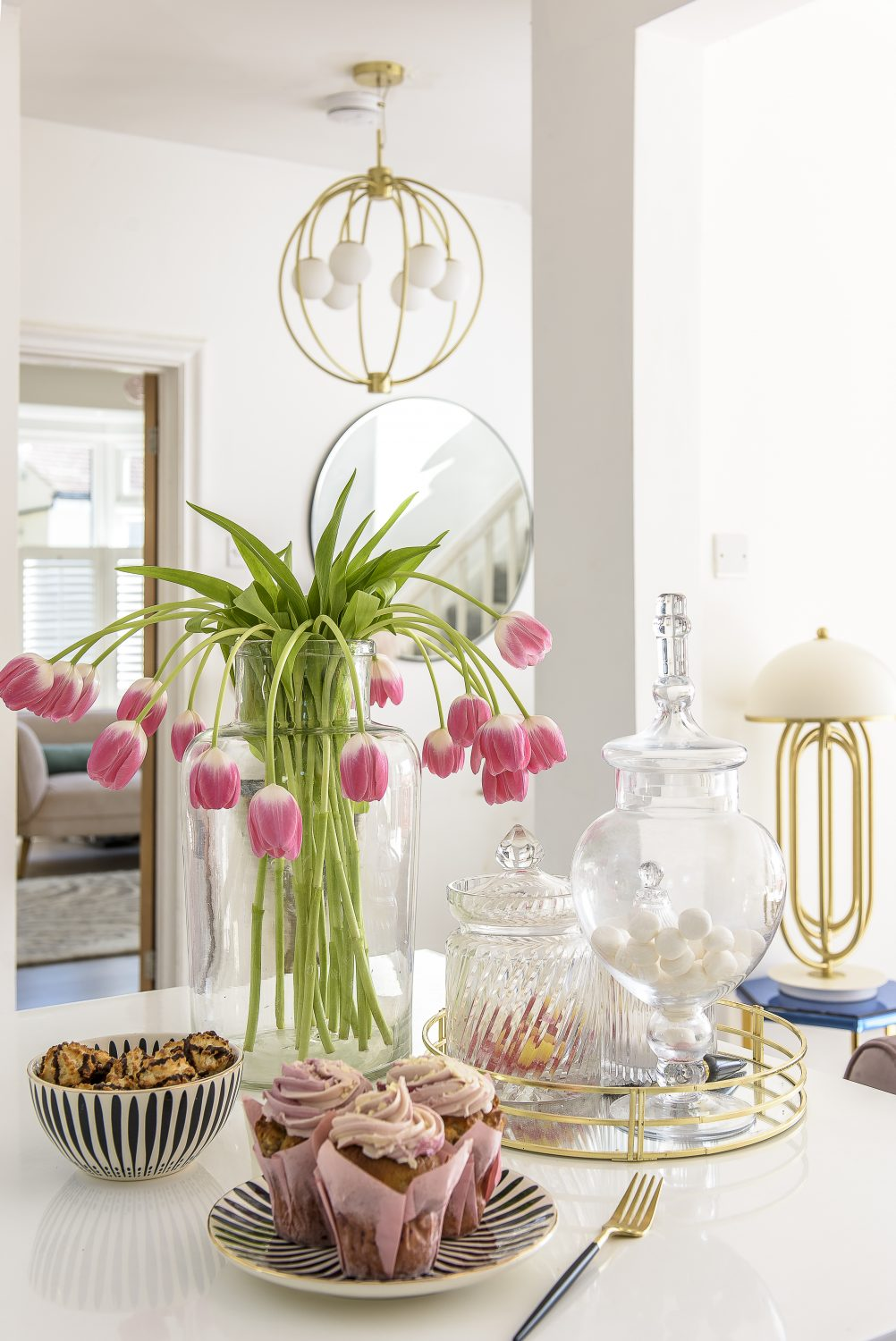 Bonbon jars and gold highlights on the gleaming white kitchen countertop
