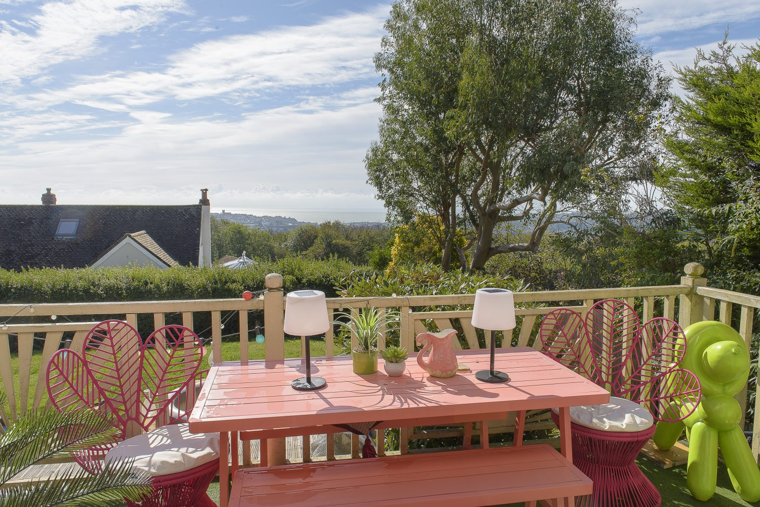 The deck on the south side of the house has an enviable panoramic sea view. Cat bought the Urban Balcony pink leaf chairs from HomeSense. A vivid green balloon poodle sculpture and bubblegum pink bench add to the kitch charm