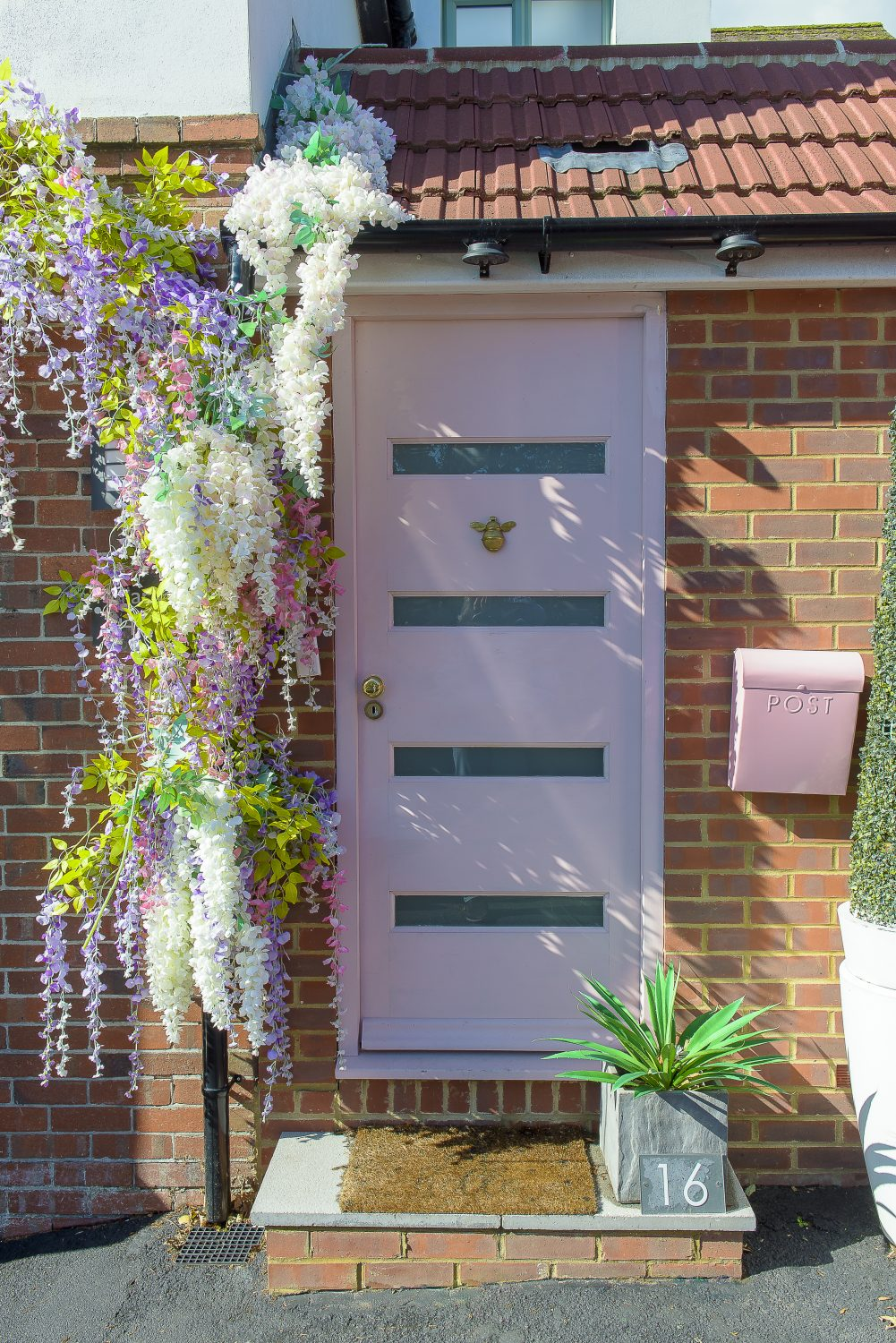 Right: Even the front door, with its brass bumblebee knocker, has been given the powder pink treatment, festooned with faux wisteria