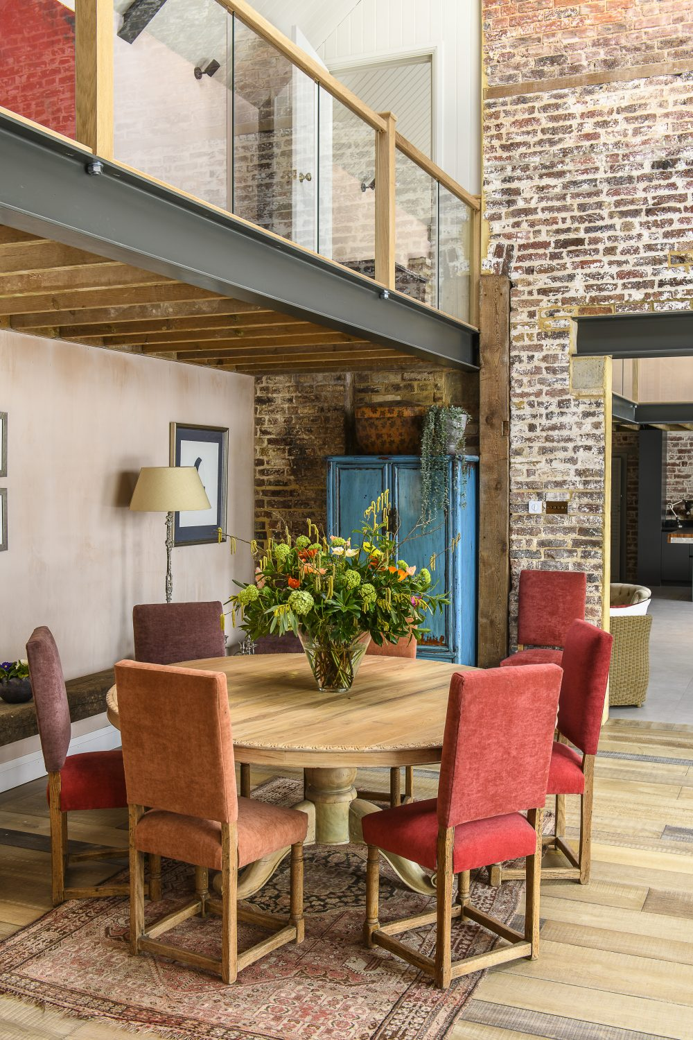 Unfinished plaster complements the exposed brickwork next to a dining area in the spacious open-plan living room