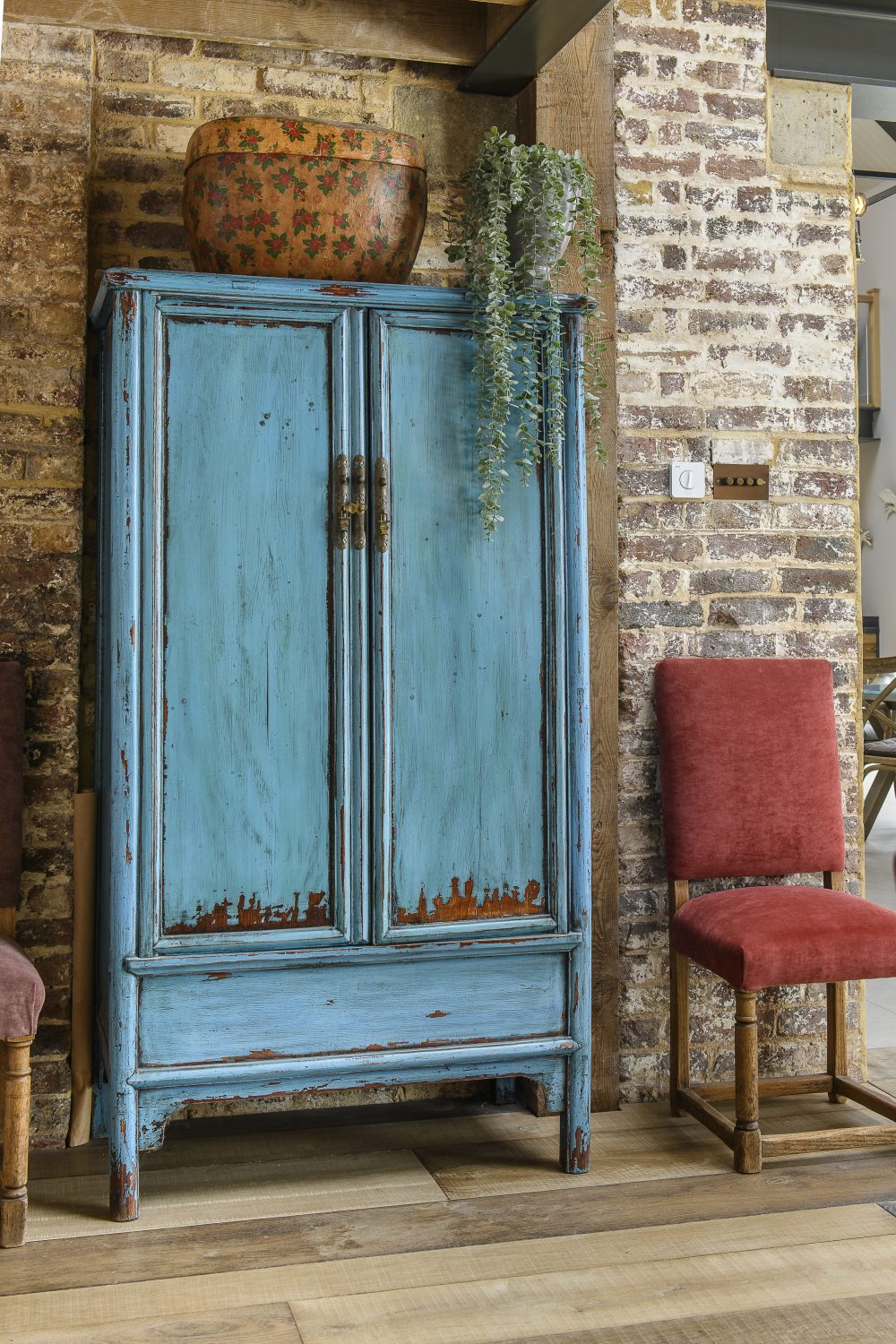 """A bright turquoise Chinese cupboard is one of the many Asian influences throughout the barn. """"I've had that cupboard for so many years,"""" says the owner. """"It follows me everywhere!"""""""