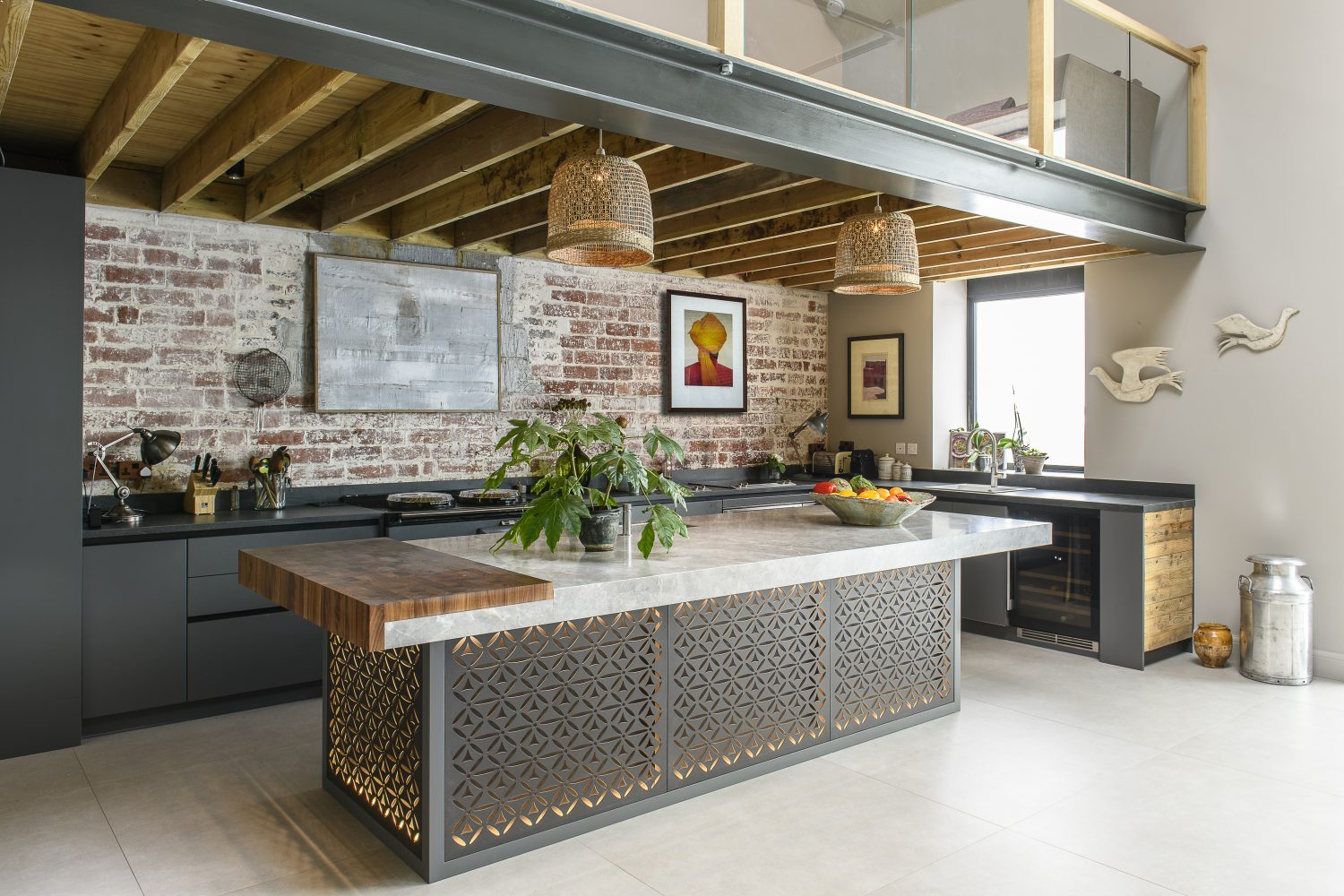"""The wall colour in the kitchen is Oak Apple from Fired Earth, a lighter colour is used here as a contrast; the kitchen nestles under part of the mezzanine. Above the cleverly illuminated island unit, what appear to be bespoke lamp shades are in fact upturned wastepaper baskets slotted over the existing shades. """"I hate seeing the light source,"""" the owner explains, """"this way you get the diffusion of light but the bulb is invisible."""""""