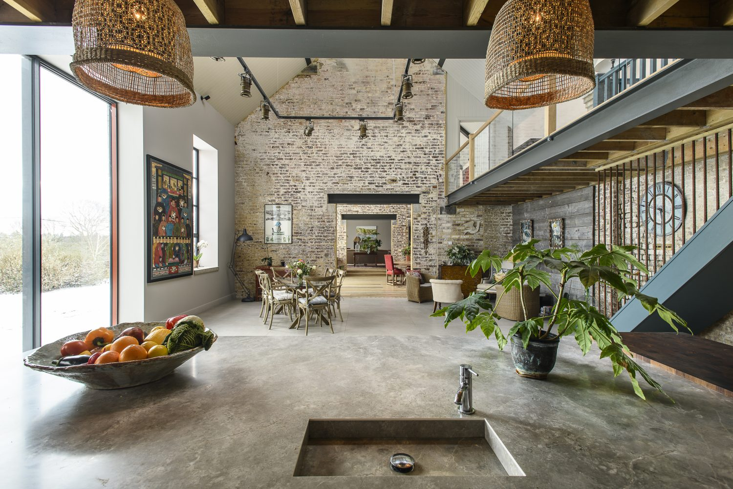 The original internal dividing walls have been knocked through so that your eye is drawn down the length of the building from the kitchen at one end to a fireplace at the other. A mezzanine expands over the sitting room and the kitchen, linked by a long glass balcony