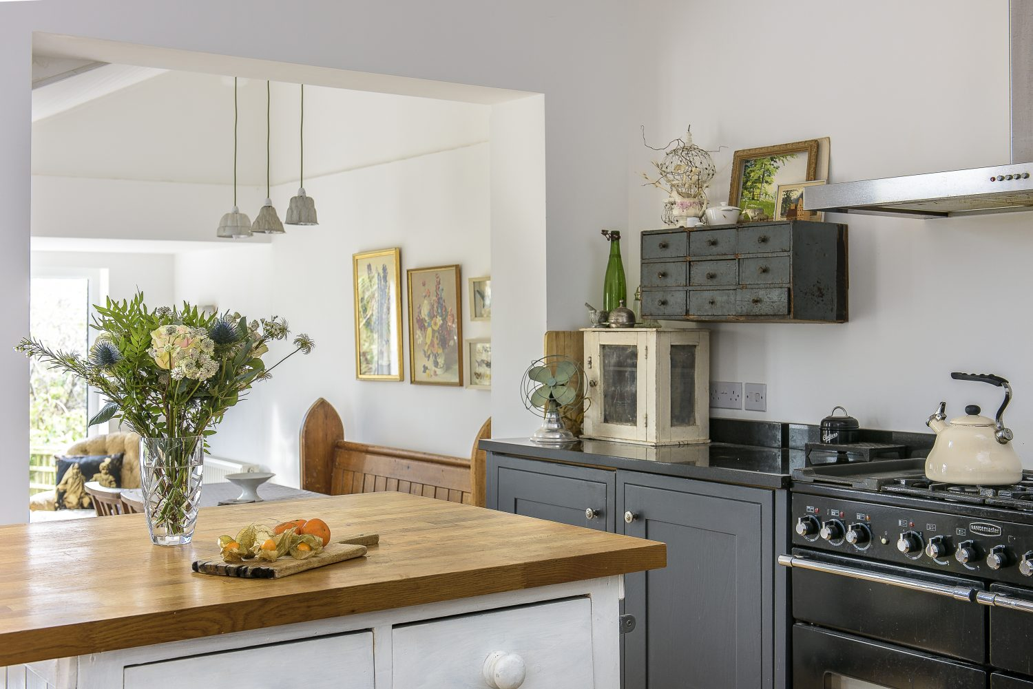 Susan created the central island from two old dressers with a new wooden worktop on top. Storage in this room includes an old white meat safe, sitting on the counter, with a set of vintage industrial drawers, painted black, on the wall above it.