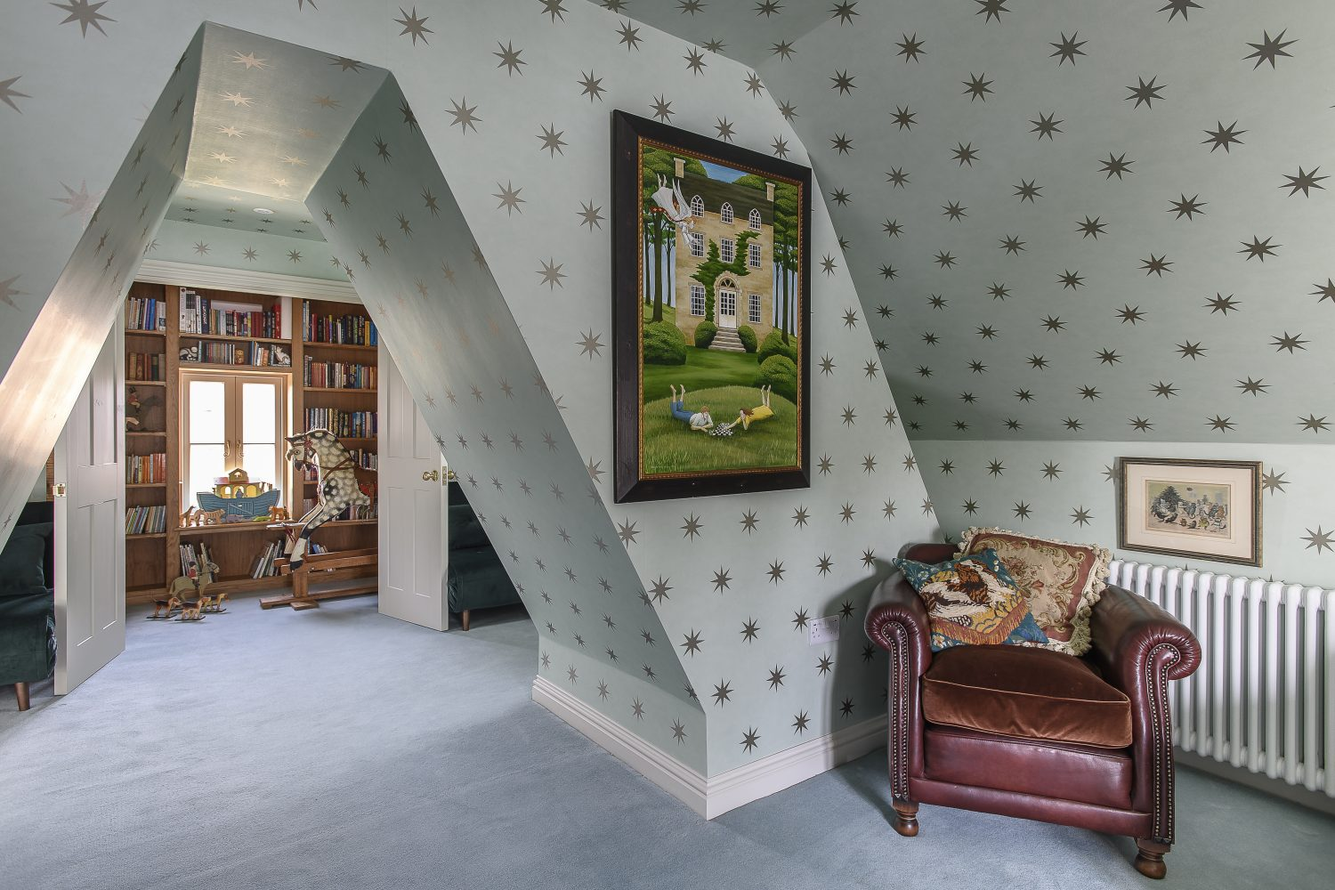 The attic is a space which has been designed with the couple's grandchildren in mind. This airy, dreamy space, tucked under the eaves, is papered in stars