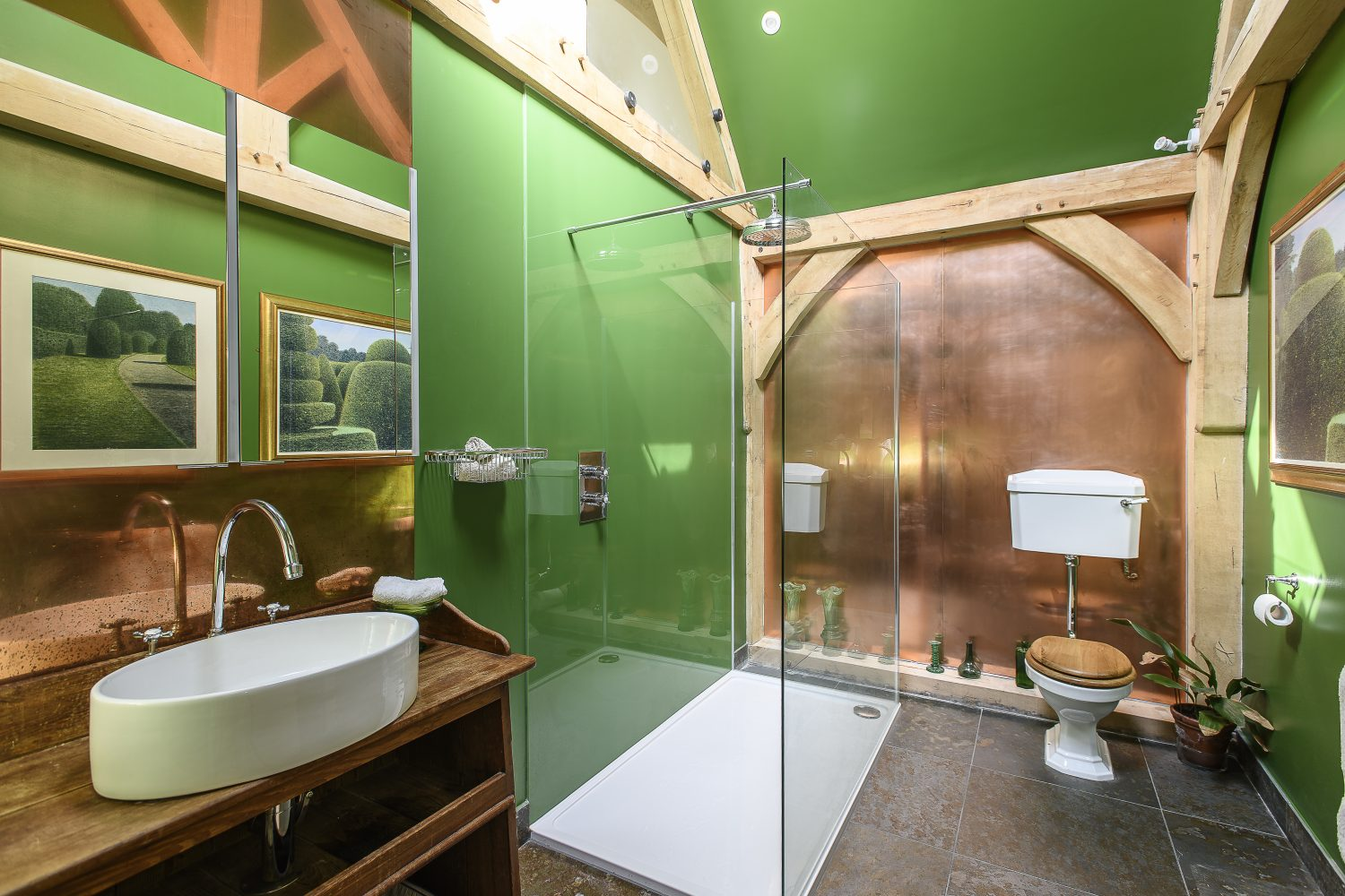 The master bedroom's vibrantly green and spacious ensuite features a copper splashback and wall below its soaring vaulted ceiling. The washstand once served as a babies' changing station