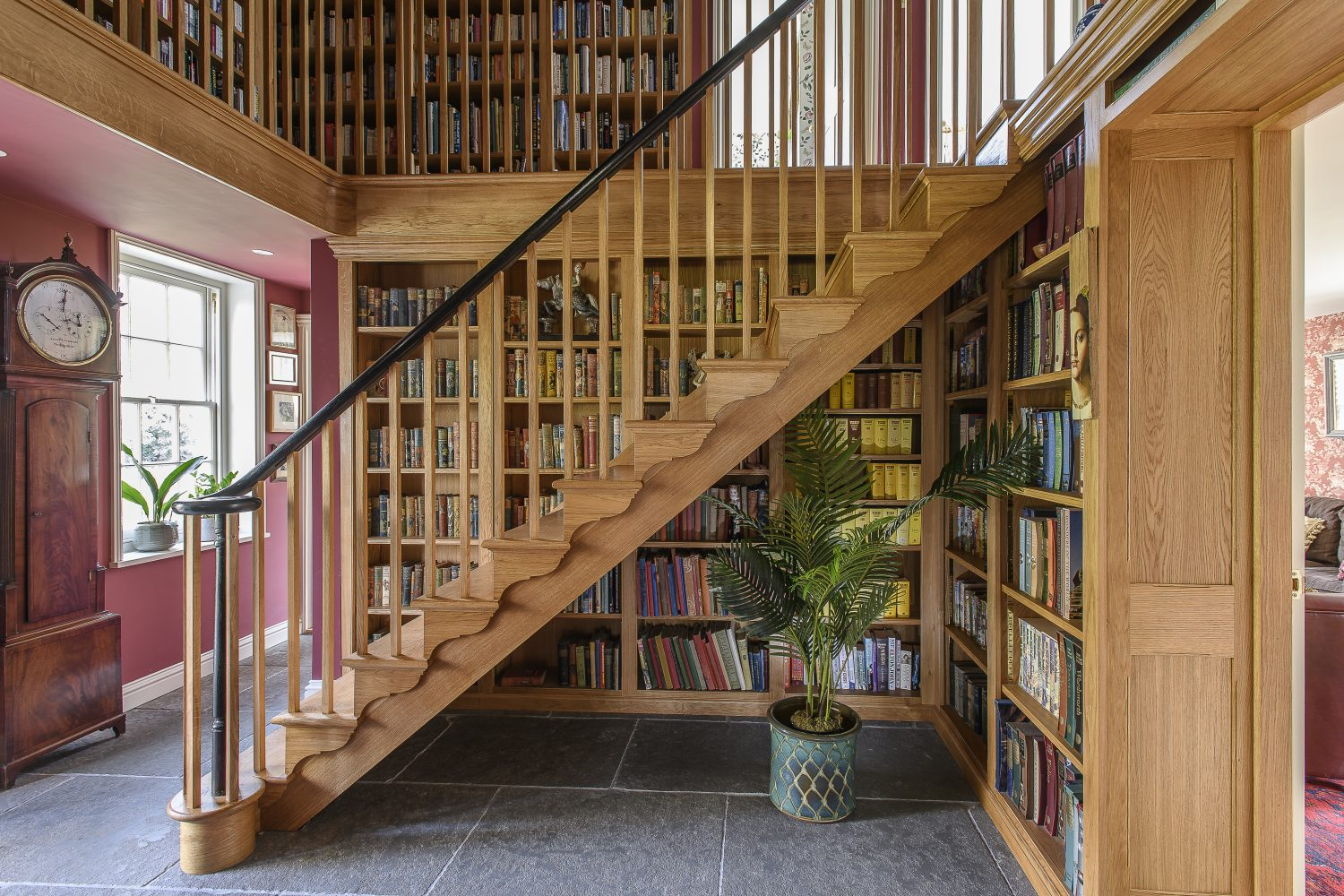 A double-height, oak-framed atrium is lined with fabulous books and objects