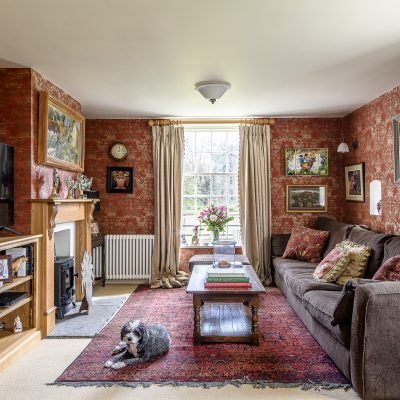 The sitting room exudes warmth and comfort with a palette of rich reds and squashy sofas