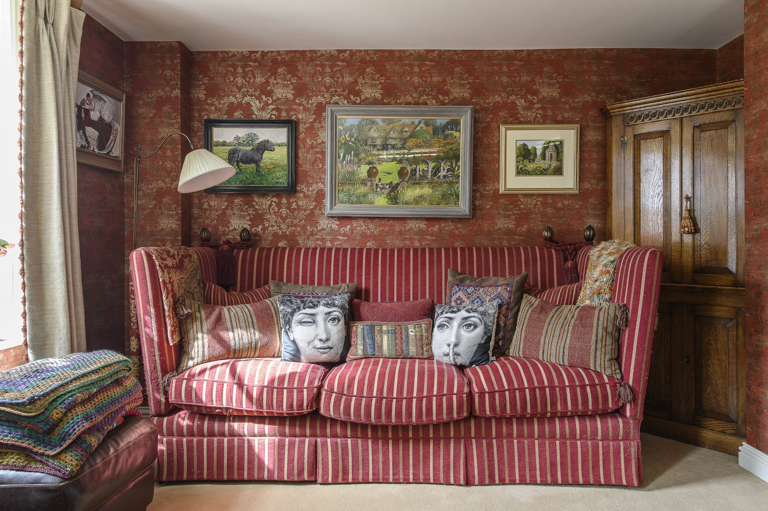The sitting room is papered in Classic Silks by Galerie. Playful Fornasetti cushions nestle on the sofa below some of Tim and Eve's favourite artworks